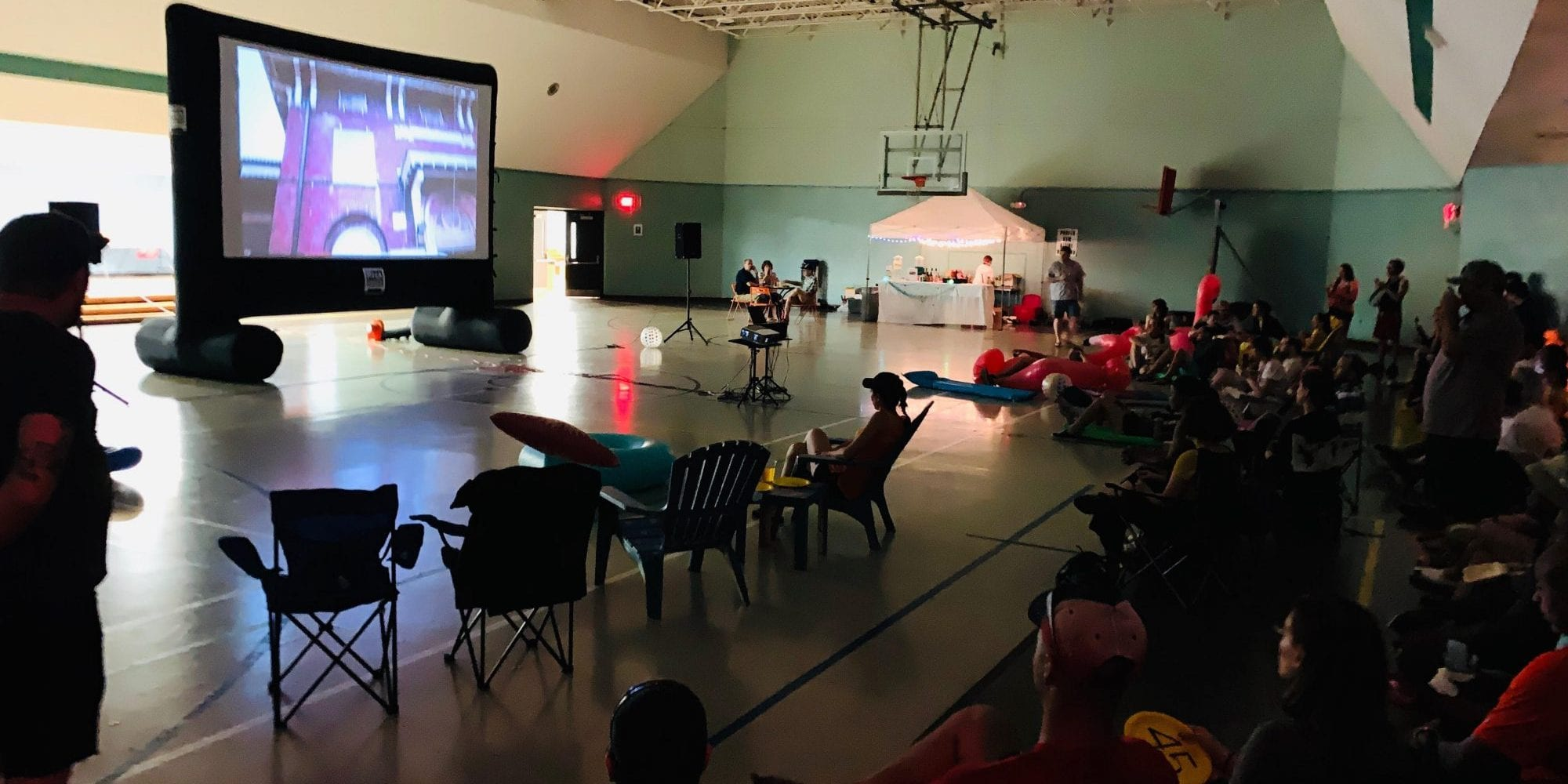 Neighbors gather in the Marquette Rec Center for a movie night fundraiser.