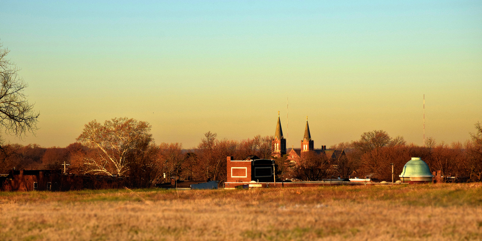 The steeples of St. Cecilia and the dome of the Virginia Theater as seen from Minnesota and Hill Park in Dutchtown, St. Louis, MO.